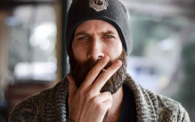 Hipster mit Bart und Zigarette
