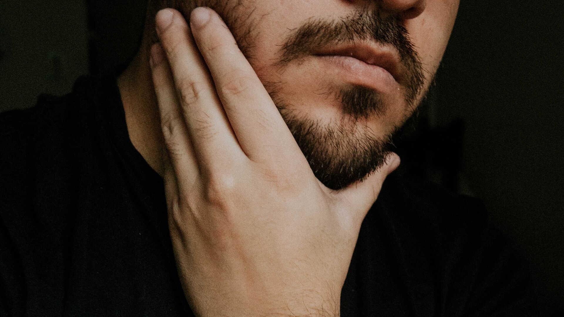 Mann berührt Bart