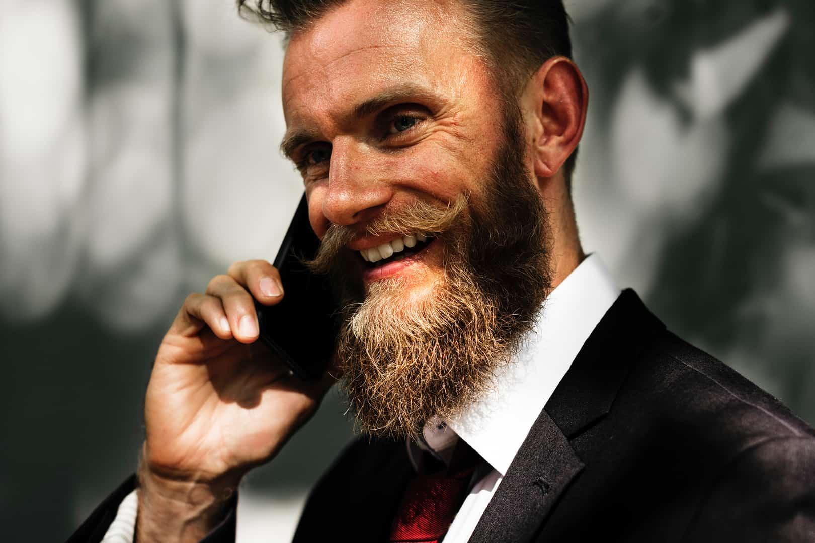 Mann mit gezwirbelten Bart telefoniert